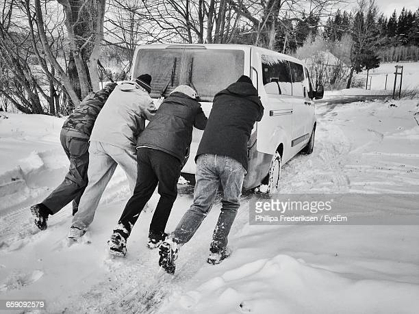 Rear View Of Friends Pushing Van On Snow Covered Field