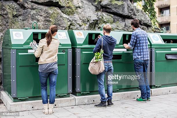 Rear view of friends putting recyclable materials into recycling bins