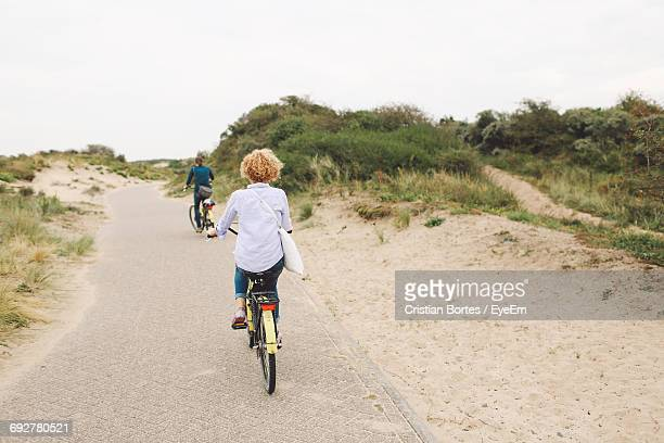 Rear View Of Friends Riding Bicycles On Footpath At Beach