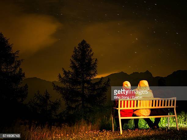 Rear View Of Friends Sitting At Park Bench On Field Against Star Field At Night