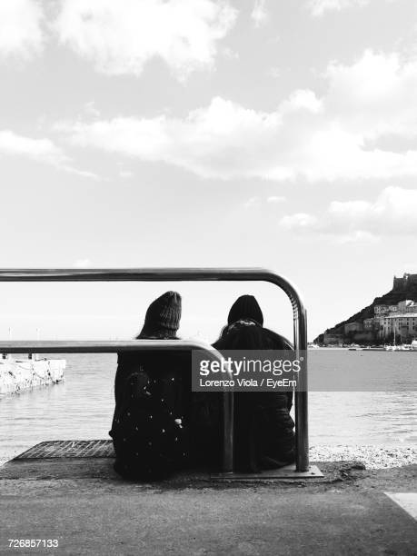 Rear View Of Friends Sitting On Jetty While Looking At Lake Against Sky