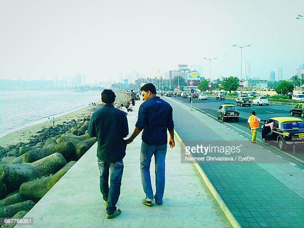 Rear View Of Friends Walking On Retaining Wall By Sea At Marine Drive