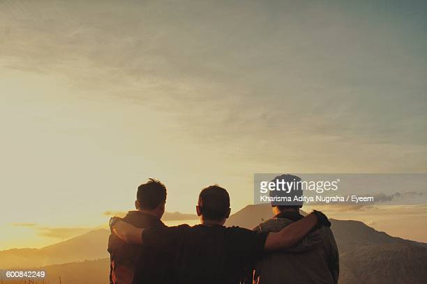 Rear View Of Friends With Arms Around Standing Against Sky During Sunrise