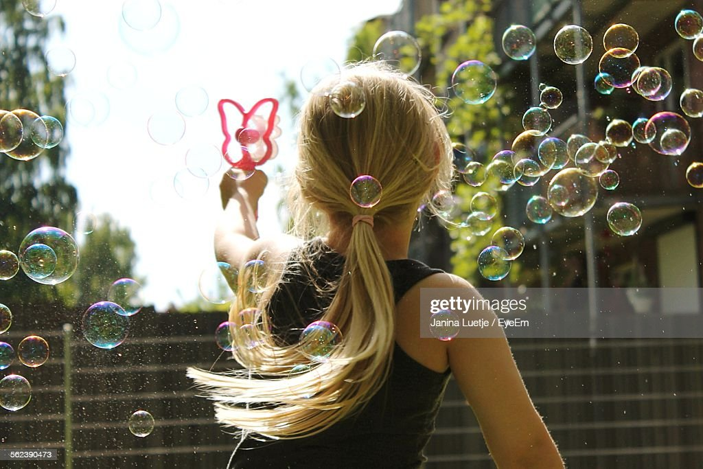Rear View Of Girl Blowing Bubbles Outdoors : Stock Photo
