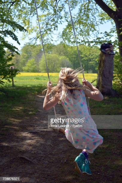Rear View Of Girl Enjoying On Swing At Park
