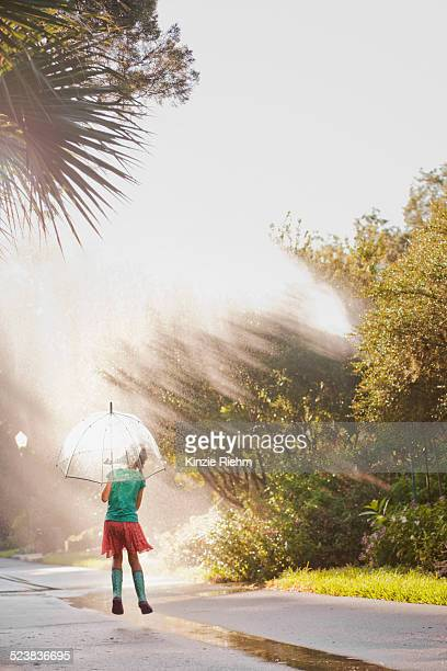 Rear view of girl holding up umbrella and jumping puddles on street