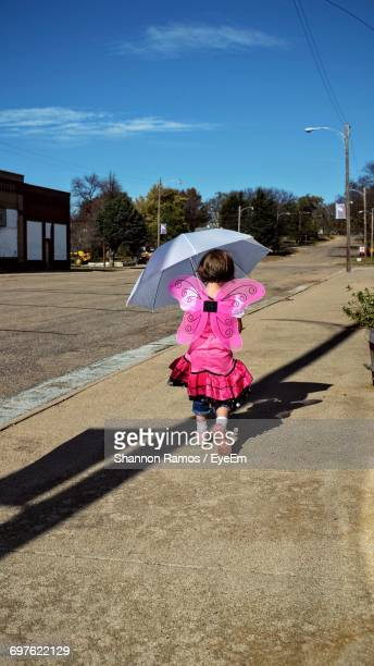 Rear View Of Girl In Angel Costume Holding Umbrella While Walking On Sidewalk