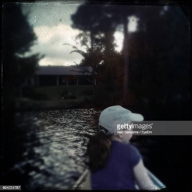 Rear View Of Girl In Boat On Lake