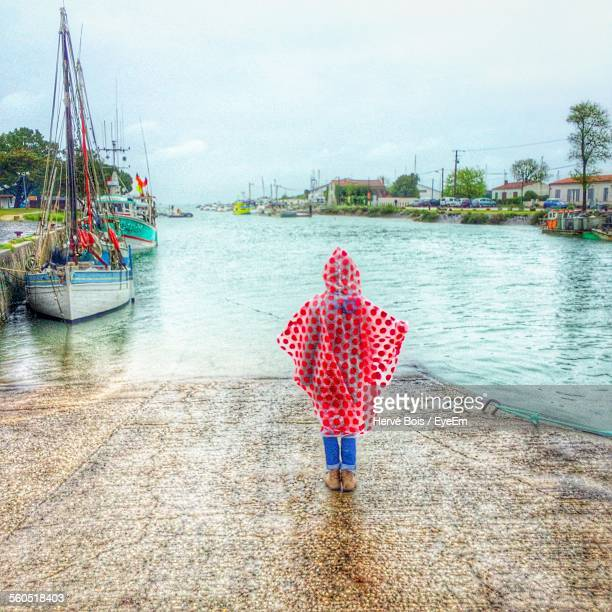Rear View Of Girl In Raincoat At Jetty
