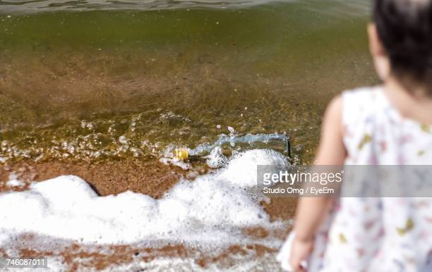 Rear View Of Girl Looking At Abandoned Bottle On Shore