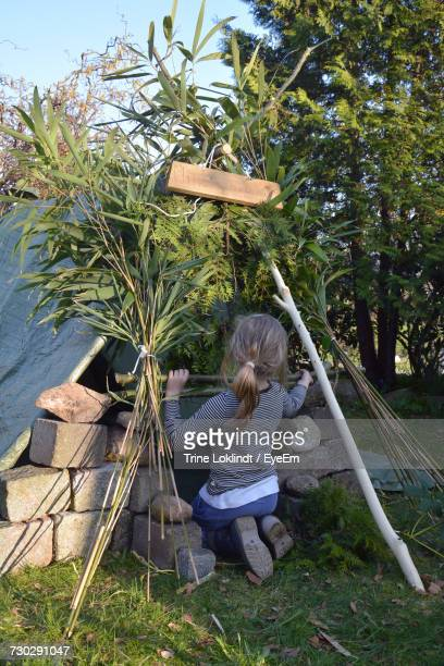 Rear View Of Girl Making Tent On Field