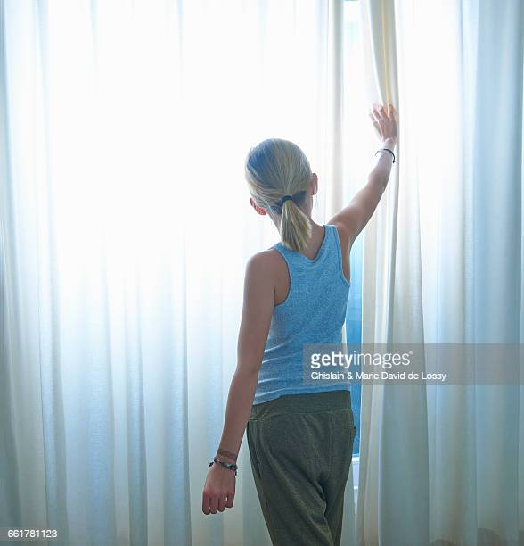 Rear view of girl peering through net curtained window