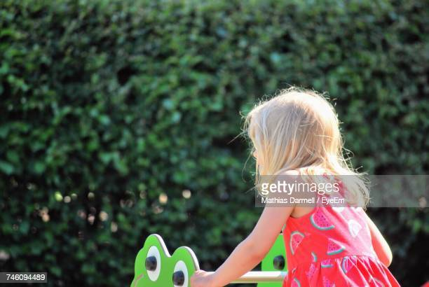 Rear View Of Girl Playing In Park Against Plants