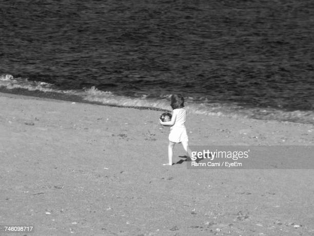 Rear View Of Girl Playing On Shore At Beach