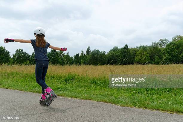 Rear view of girl rollerblading in park