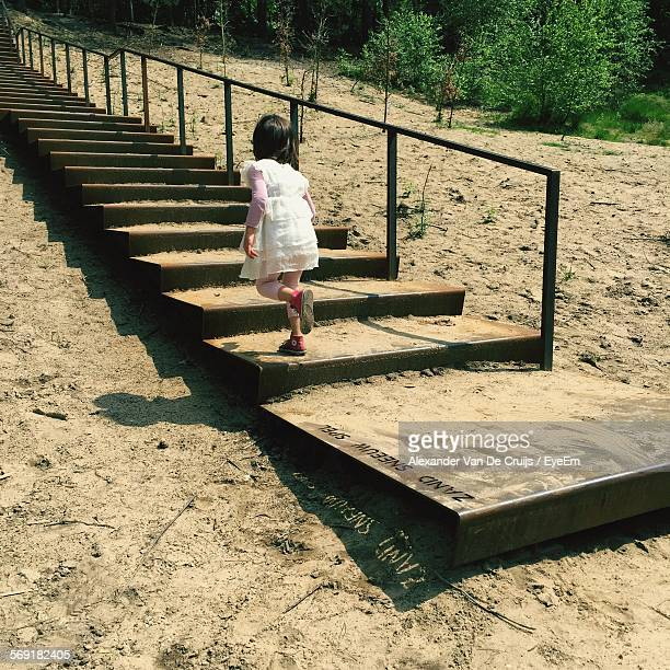Rear view of girl running on staircase in beach
