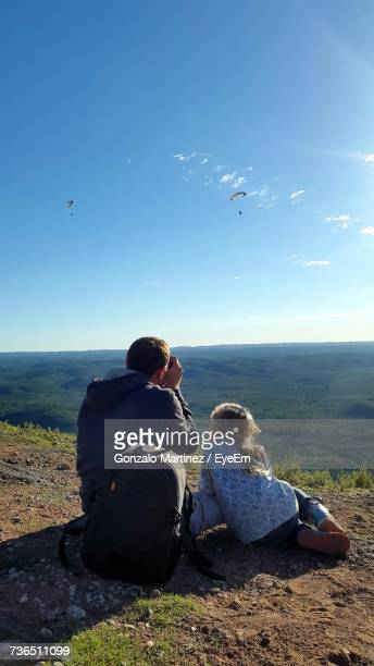 Rear View Of Girl Sitting By Father Photographing Parachutes In Sky