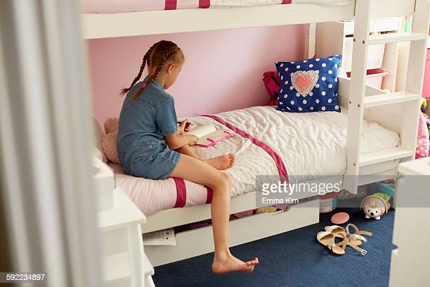 Rear view of girl sitting on bunkbed writing in notebook