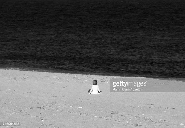 Rear View Of Girl Sitting On Shore At Beach