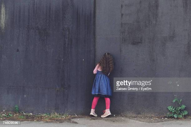 Rear View Of Girl Standing Against Black Wall