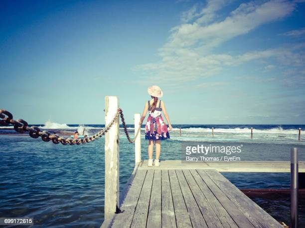 Rear View Of Girl Standing By Railing On Jetty At Sea Against Blue Sky