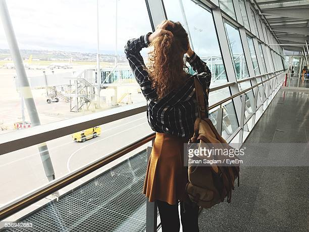 Rear View Of Girl Standing On Pedestrian Walkway Bridge At Airport