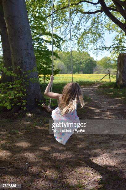 Rear View Of Girl Swinging In Park