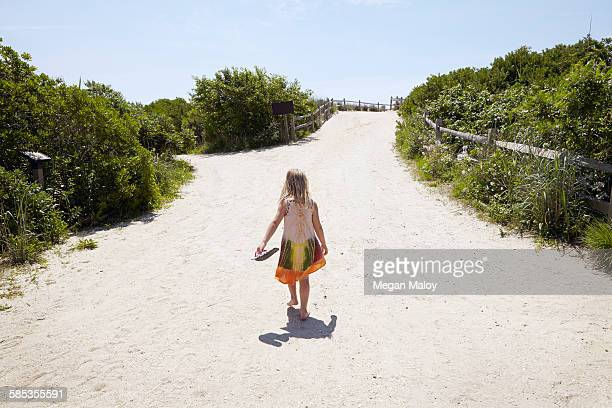 Rear view of girl walking barefoot to beach
