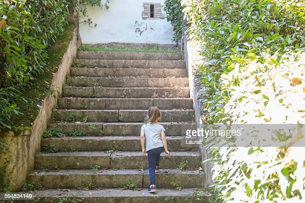 Rear view of girl walking up steps