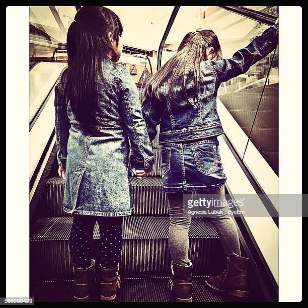 Rear View Of Girls Standing On Escalator