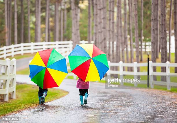Vista posteriore di ragazze con ombrelloni in pioggia