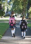Rear view of girls with backpacks walking down sidewalk