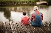 Color image of a senior man sitting on an old, wooden dock while fishing with his young great grandson.
