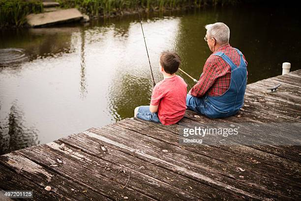 Rear View of Grandpa Fishing With His Great Grandson