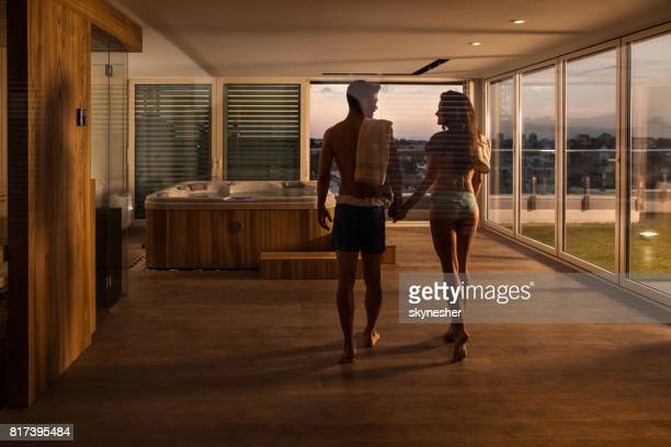 Rear view of happy couple walking towards the hot tub in their penthouse.