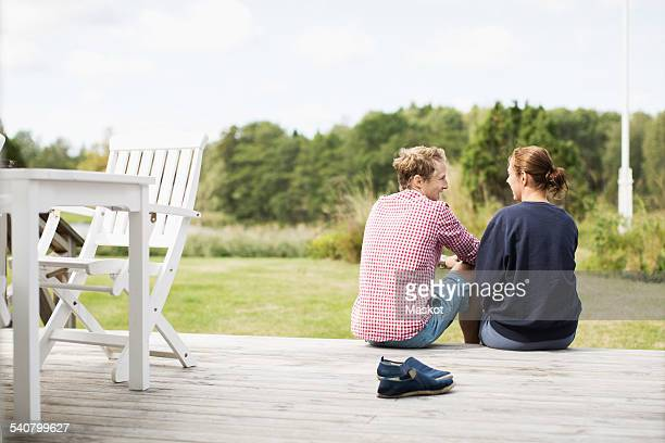 Rear view of happy mature couple communicating on porch