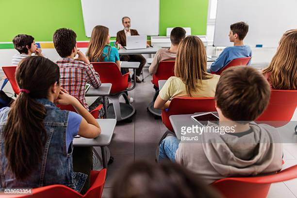 Rear view of high school students attending a class.