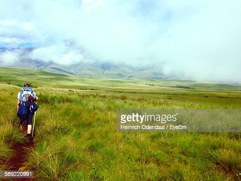 Rear View Of Hiker On Field Against Cloudy Sky