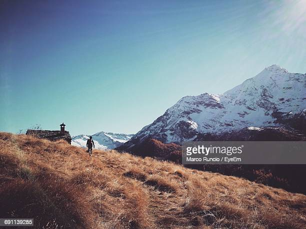 Rear View Of Hiker Walking On Field By Snowcapped Mountains Against Sky