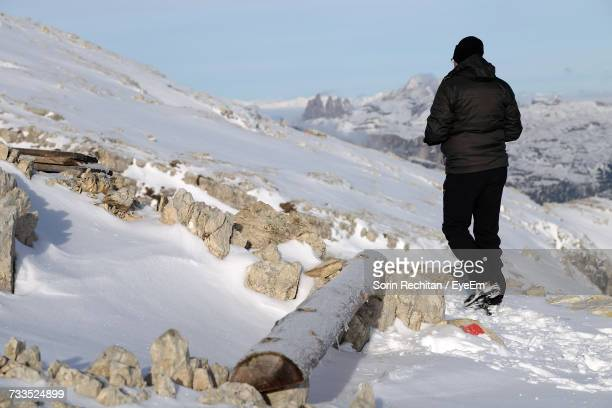 Rear View Of Hiker Walking On Snow Covered Mountain Against Sky