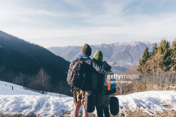 Rear view of hiking couple looking out over lake and mountains, Monte San Primo, Italy