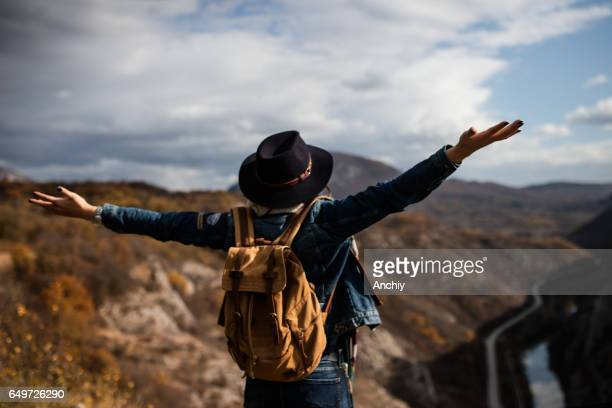 Rear view of hiking girl with her arms wide open on top of the cliff