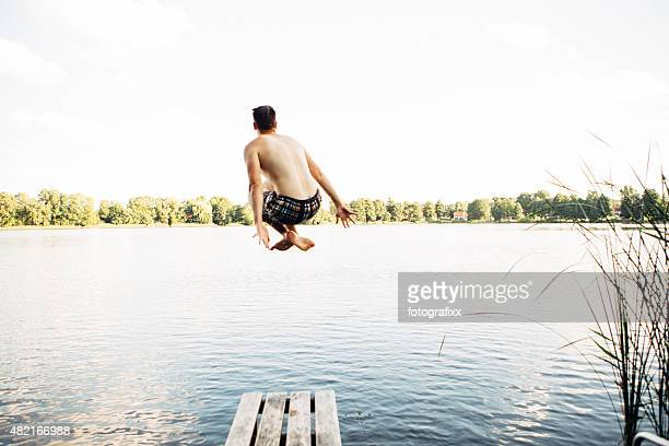 rear view of jumping young from jetty into a lake