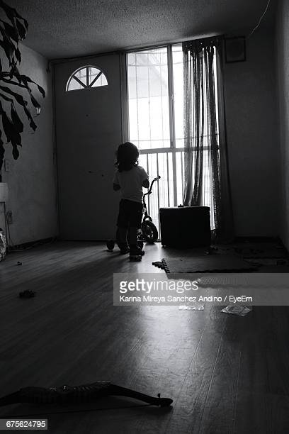 Rear View Of Kid With Bicycle Standing By Window At Home