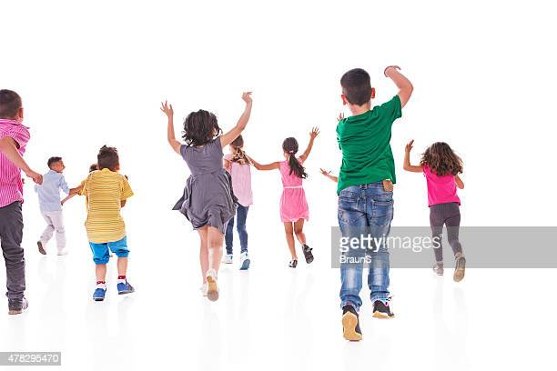Rear view of large group of children running.