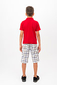 Rear view of little boy standing over white background. Vertical composition. Image taken with Nikon D800 and developed from Raw format. Little boy wearing a red t-shirt, striped shorts.