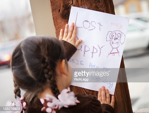 Rear view of little girl posting lost puppy sign