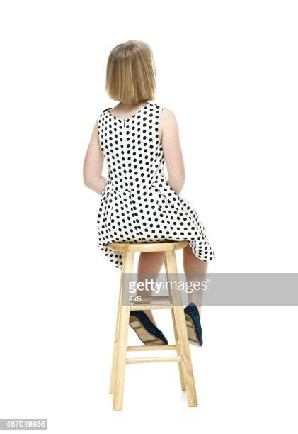 Rear view of little girl sitting on stool