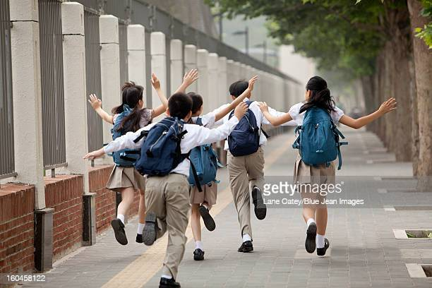 Rear view of lively schoolchildren in uniform on the way to school