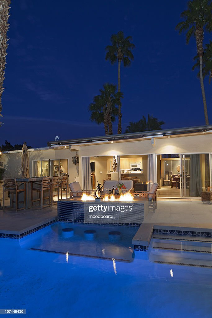 Rear view of luxury villa at night time with lit fire : Stock Photo